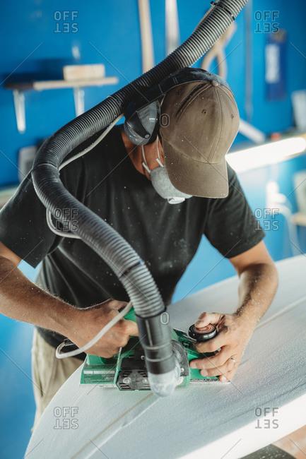 Worker in protective mask adjusting details surfboard in workshop