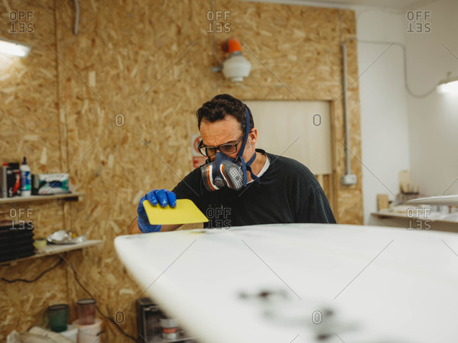 Adult craftsman in protective mask and gloves polishing white surfboard while working  in small workshop