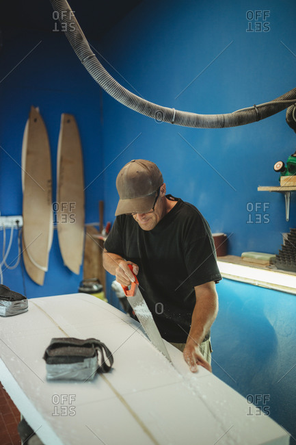 Professional man sawing plank while producing surf board in small workshop with blue walls