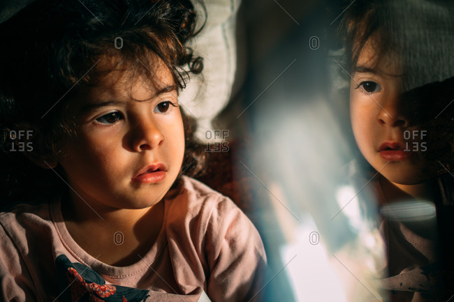 Curious kid with curly hair sitting near illuminated glass while resting at home at night