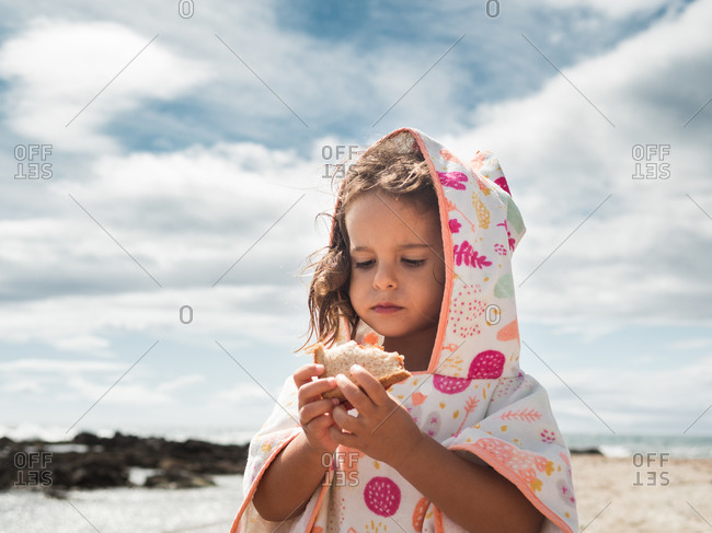 Girl in hooded apparel chewing fresh bread while resting against cloudy sky on sunny summer day on beach