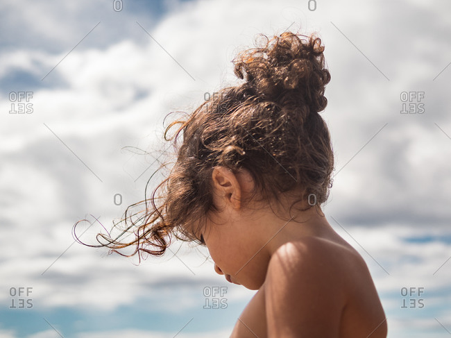 Side view of cute little girl with pigtails against blue sky