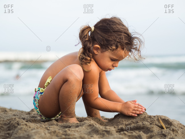 Side view of cute little girl with pigtails trying to make sand castle while playing on beach near waving sea on resort