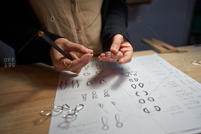 Cropped unrecognizable woman jewelry designers with a pencil in hand making jewelry drawings on a paper on a wooden table