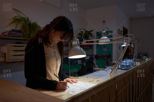 Beautiful brunette woman jewelry designers with a pencil in hand making jewelry drawings on a paper on a wooden table