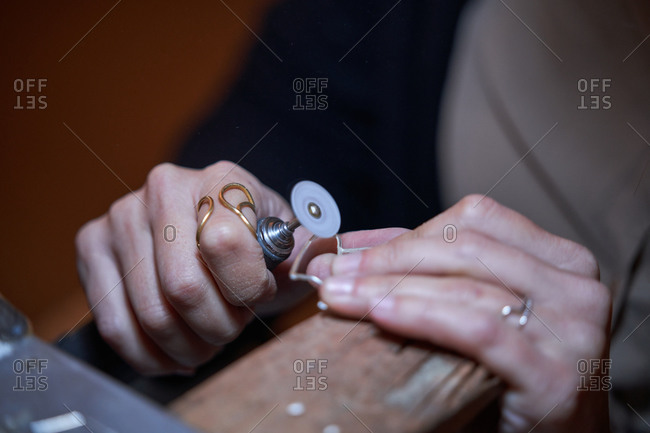 Cropped unrecognizable jeweler woman working in a jewelry shop, hands detail with jewelry and tools