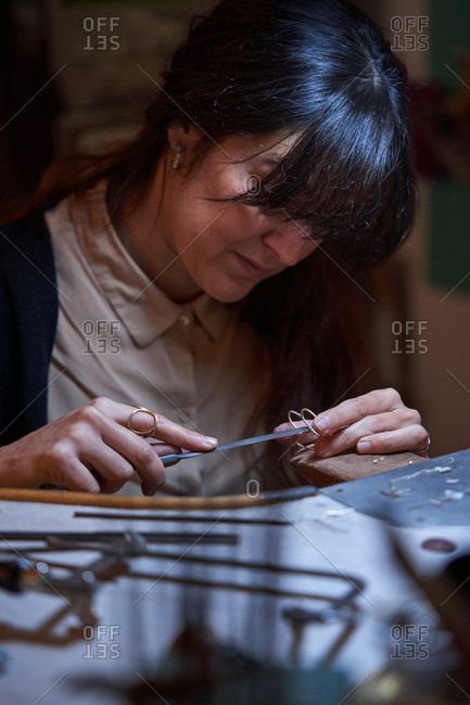 Beautiful artisan jeweler woman with working in a jewelry shop, hands detail with jewelry and tools