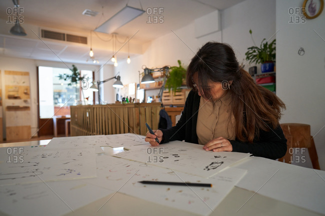 Woman sitting at a table with a pencil drawing jewels on paper