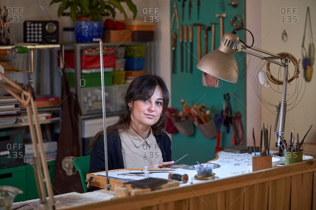 Beautiful artisan jeweler woman working in a jewelry shop with tools and a light bulb