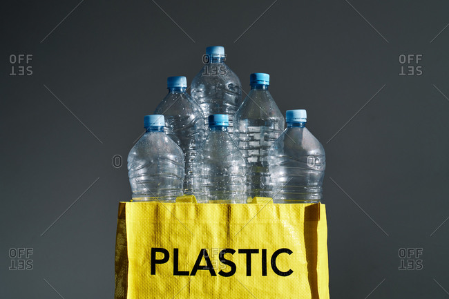 Heap of empty water bottles in yellow bag with recycle sign on gray background in studio