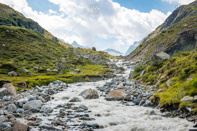 Landscape with beautiful shallow mountain river running on rocky bed in narrow valley in Austria
