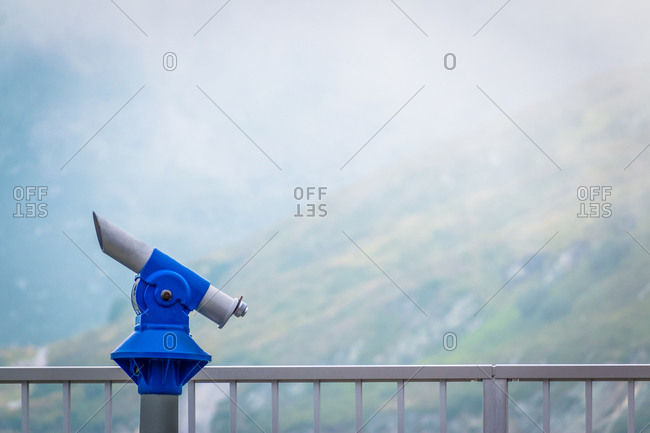 Viewing platform with coin-operated telescope in Austrian mountains in misty weather with zero visibility