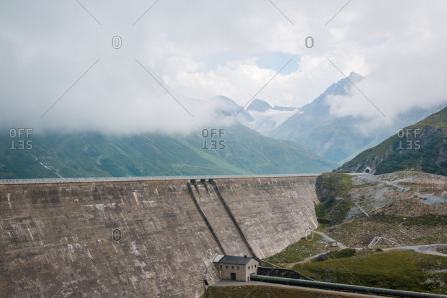 High alpine road on big dam on background with misty cloudy mountains in Austria
