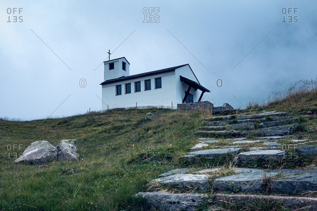 Charming landscape of small white church on top of green valley with stony way up in Austria
