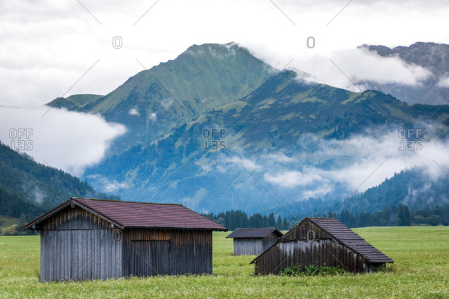 Picturesque landscape of small charming house on lawn with juicy green grass nearby evergreen forest and high mountains in Austria