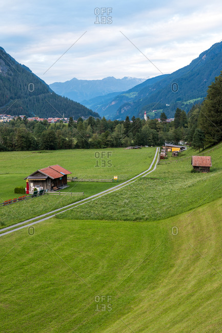 Lovely farm shacks located near road in green valley against mountain ridge on cloudy day in Austria