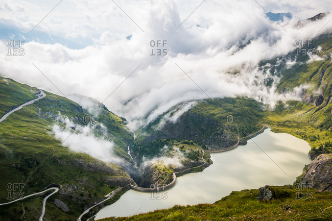 Thick white clouds floating over green mountainous terrain with tranquil lake in Austria