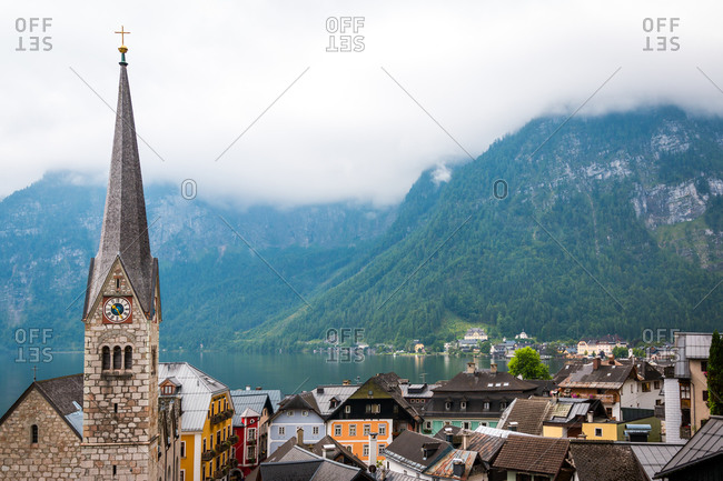 August 10, 2017: clean pond with tranquil water and lovely houses of small town located near mountain ridge on cloudy day in Austria