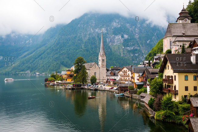 Clean pond with tranquil water and lovely houses of small town located near mountain ridge on cloudy day in Austria