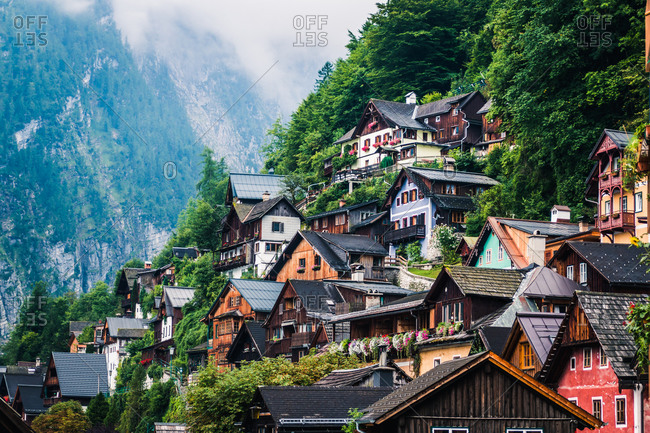 Cozy houses of small settlement located near forest on mountain slope on cloudy day in Austria