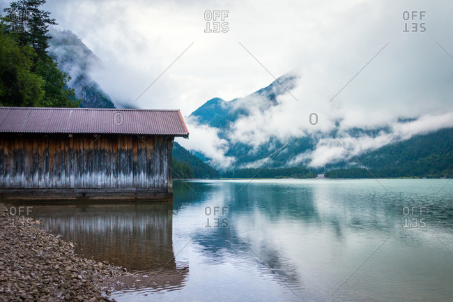 Shabby shed for boats located near tranquil water of pond near mountain ridge on cloudy day in Austria