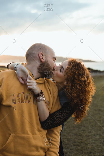Young bald bearded man in yellow hoodie and jeans shorts being embraced by happy curly haired girlfriend in dress and denim vest while standing together kissing with closed eyes on meadow