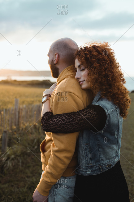 Young bald bearded man in yellow hoodie and jeans shorts being embraced by happy curly haired girlfriend in dress and denim vest while standing together on meadow