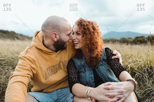 Young bald bearded man in yellow hoodie and jeans shorts embracing happy curly haired girlfriend in dress and denim vest while sitting together on meadow and talking