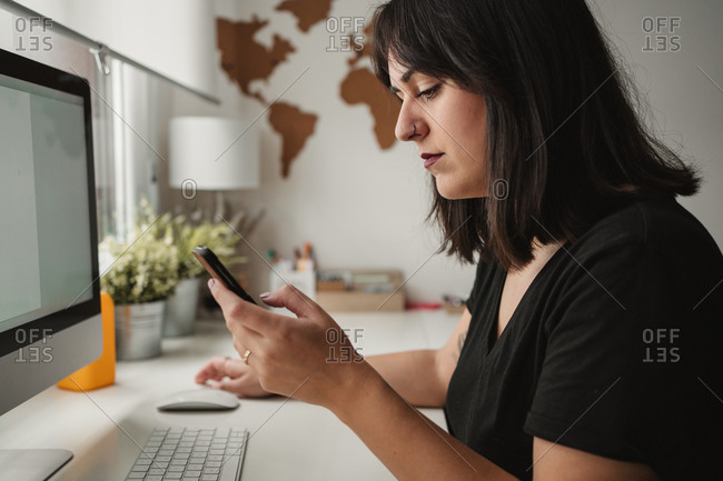 Side view of crop focused woman with dark hair messaging on cellphone while sitting with desktop computer in office in Paris