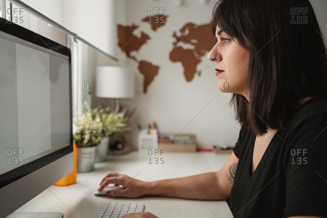 Side view of concentrated dark haired female employee focusing on screen and typing on computer while sitting at table in light office in Paris