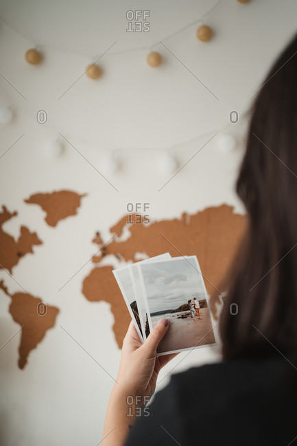 Crop back view of faceless female tourist watching pictures and remembering past journey while standing in front of world map at home in Paris