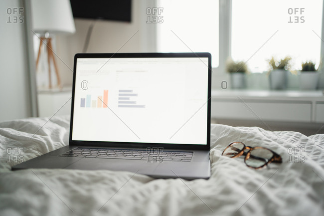 Opened computer with diagrams on screen and spectacles on bed in modern apartment in Paris