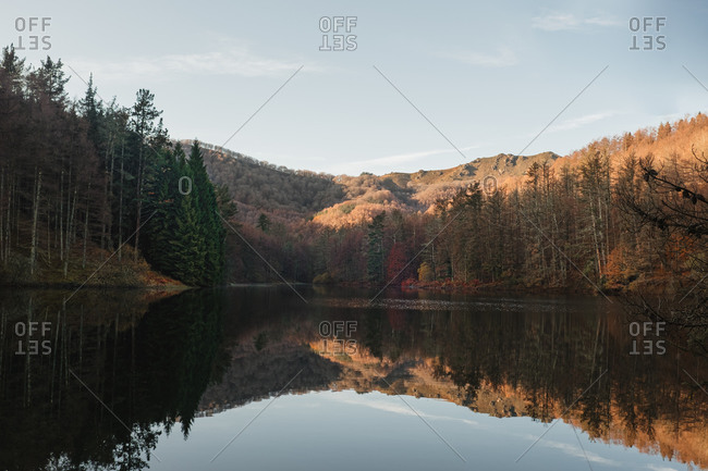 Scenic landscape with green and yellow forest and hills reflected in calm dark water of beautiful lake in sunny day