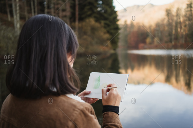 Back view of female artist standing next to beautiful lake surrounded with forest in autumn day and drawing in notebook