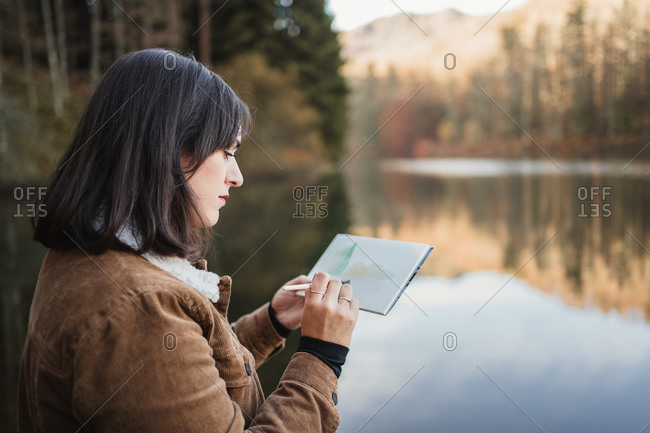 Woman standing at lakeside and drawing in notebook