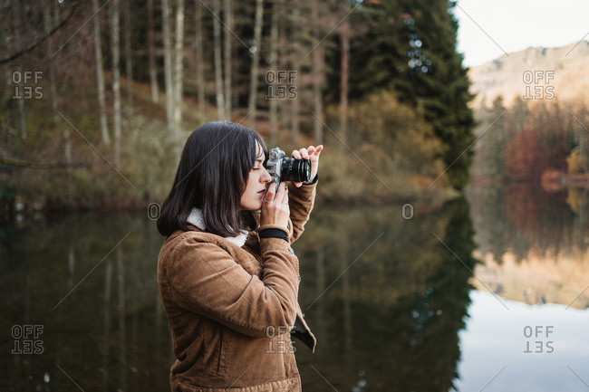 Side view of young female traveler in brown jacket taking picture with photo camera while standing next to lake surrounded with forest in autumn day