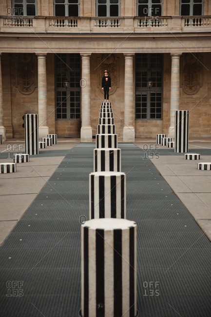 Traveler exploring city standing on white and black pole in square of Paris