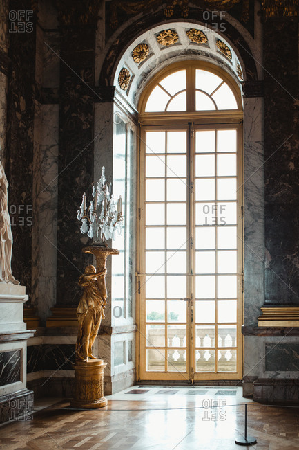 Room of castle with colorful big door and statue with lamp in Paris