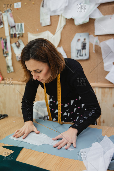 Woman using sharp scissors to cut garment detail from fabric while sitting at table in tailor workshop