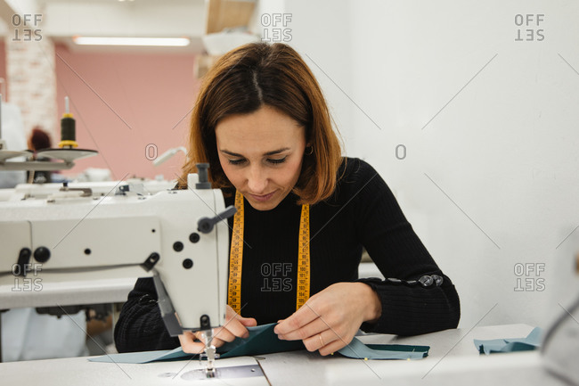 Adult woman sitting at table and making garment part on sewing machine while working in professional studio
