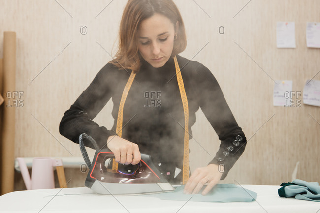 Happy adult woman ironing part of custom apparel and smiling while working in dressmaking studio