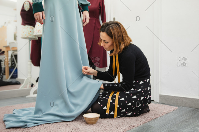 Dressmaker kneeling on carpet and fitting skirt of custom gown while working in professional studio