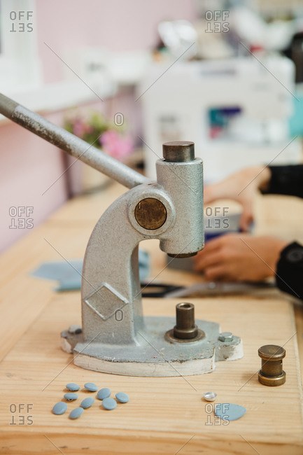 Crop anonymous person hands pulling lever of button maker on table in professional dressmaking workshop while making garment