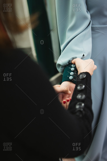 Female tailor attaching buttons with pins on sleeve of dress on model arm during work in professional workshop