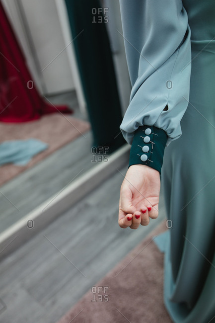 Attached buttons with pins on sleeve of dress on model arm in professional workshop