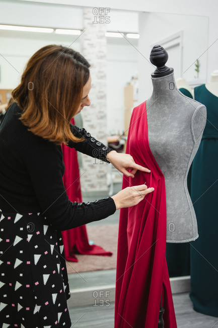 Anonymous woman using pins to attach red fabric to mannequin while making dress in professional tailor studio