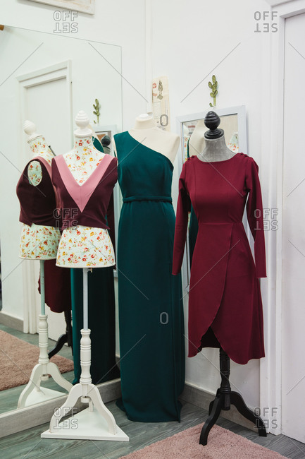 Mannequins with trendy custom apparels placed near mirror in corner of dressmaking studio