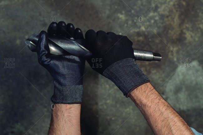 Infrared unrecognizable man in gloves swinging drill bit during work process