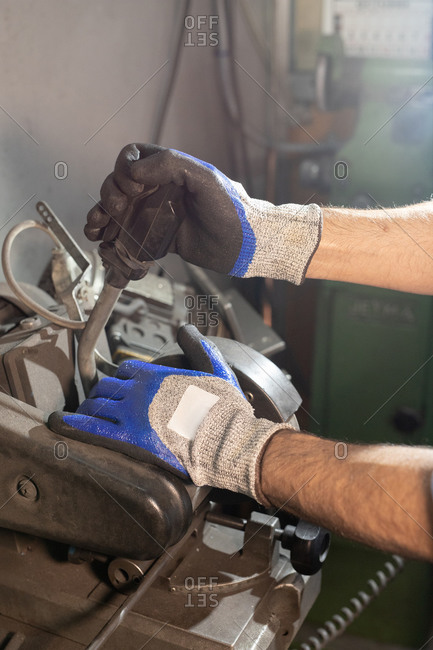 Crop faceless male in gloves creating details while working on industrial machine at workshop