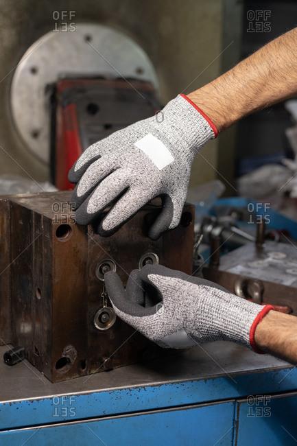 Unrecognizable handyman using machine on factory